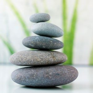 5 stones balanced one atop of he other to represent a balanced and harmonious feeling.